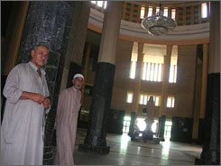 Two employees of the Baghdad Central Railway Station greet visitors. The station has been largely devoid of passengers despite a recent $6-million renovation.