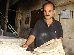 Saeed Hady Maktoof stacks up flat bread before customers enter his bakery in Baghdad.