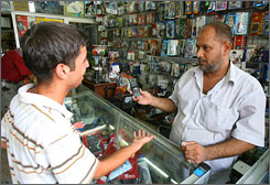 An Iraqi buys a mobile phone handset from a shop in Baghdad on Aug. 13. Sending text messages and swapping or downloading ringtones have become the highlight of entertainment in Baghdad.