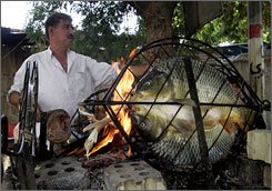 An Iraqi cook grills river fish in Baghdad to prepare mazgouf.