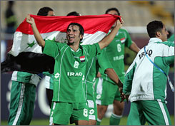 Samer Mujbel holds up an Iraqi flag to cheering crowds as he celebrates 1-0 victory over South Korea on Tuesday with teammates in the Asian Games Soccer Men's semifinals in Qatar.