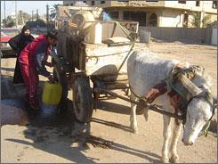 Kerosene seller Moyaid Ouda fills 20 liters of kerosene for Layla Abdel-Qader and her husband for 20,000 Iraqi dinars ($15.40).