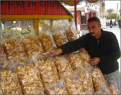 Jassim Issa, 39, sells potato chips from his sidewalk stand in Baghdad?s Karrada district. Despite declining sales, Issa says he will stay with his business for love of the chip.