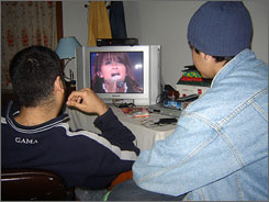 Aseel Hameed, 31, left, and his cousin Mustafa Jassem, 17, watch Shada Hassoon sing Baghdad on Star Academy.