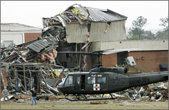 A U.S. military helicopter evacuates a patient from Enterprise High School after a tornado did severe damage to the school Thursday.