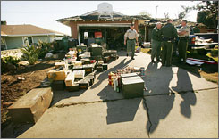 Officials stand in a driveway with a cache of ammunition Friday in Norco, Calif. Firefighters responding to a blaze at the Riverside County home Thursday found more than 1 million rounds and multiple firearms inside, authorities said.