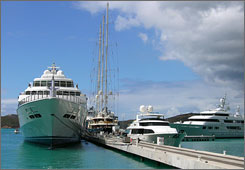 The Rising Sun, left, a 452-foot, five story megayacht is anchored next at the Yacht Haven Grande harbor in St. Thomas.
