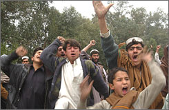 """After violence along a busy highway that left 16 Afghans dead, hundreds of people blocked the road and threw rocks at police, with some demonstrators shouting """"Death to America! Death to Karzai,"""" a reference to President Hamid Karzai."""