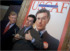 Comedian Stephen Colbert shows off his Person of the Year award while flanked by CNN senior political analyst Jeff Greenfield, moderator of the ceremony at the U.S. Comedy Arts Festival  in Aspen, Colorado.