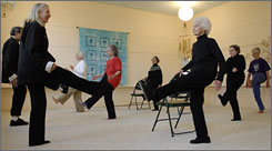 Instructor Cate Morrill, foreground left, works with Padgett, right, and her classmates in their Tai Chi class.