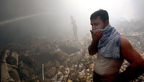 A man stands amid rubble just after a suicide car bomb exploded in Baghdad on Monday.