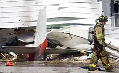 A firefighter walks by a plane that crashed into a home in Bedford Ind.