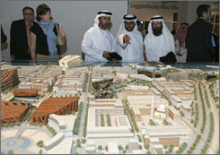 Emirati citizens look at a model of Al Saadiyat Island, on which the Louvre Abu Dhabi will be built, during the signing of a cultural exchange agreement in Abu Dhabi, United Arab Emirates, Tuesday. The deal provides for the setting up of the museum, an offspin of the Louvre in France, in the man-made island off the coast of the Gulf Arab emirate.