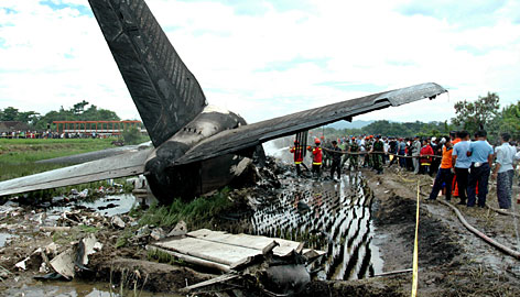 People gather around the wreckage of the plane. The blaze started at the front of the plane as it touched down at the airport, said survivors. It took more than two hours to put out the fire.