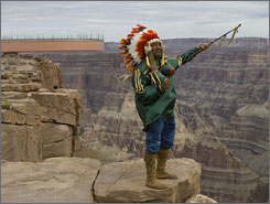 Hualapai tribe member Don Havatone stands in front of the glass-bottomed Skywalk that extends over the edge of the Grand Canyon.