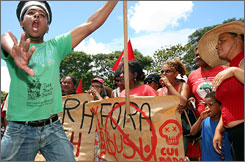 """Outside the U.S. Embassy in Brasilia, members of the Brazilian Landless Workers Movement demonstrate Thursday against the upcoming visit of President Bush and his proposal for an ethanol manufacturing alliance with Brazil. The banner reads: """"Get out Bush."""""""