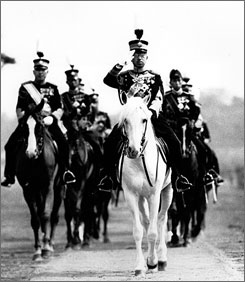 Emperor Hirohito salutes from his mount, his favorite white horse, during a military review in Tokyo in 1937.