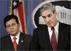 FBI Director Robert Mueller, right, listens to a question during a joint news conference with U.S. Attorney General Alberto Gonzales at the Department of Justice in this February 27, 2007 file photo.