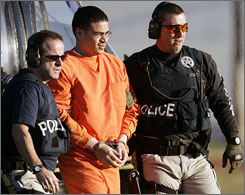 Jose Padilla, a 36-year-old U.S. citizen, is scheduled to stand trial April 16 along with two co-defendants on charges of being part of a North American terror support cell. This file photo shows Padilla, center, being escorted by federal marshals in Jan. 2006.
