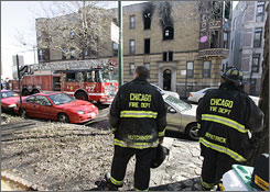 Firefighters stand outside a three-story apartment building on Chicago's North Side after a blaze there claimed 4 lives.