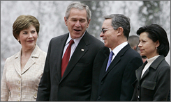 President Bush shares a light moment with Colombian President Alvaro Uribe (second from right) as U.S. first lady Laura Bush and Colombia's first lady Lina Maria Moreno de Uribe look on during an arrival ceremony in Bogota.