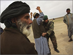 Afghan soldiers search civilians for weapons inthe desert Saturday. The government controls only part of the province,which is rife with Taliban insurgents and drug operations. About 4,500NATO troops and 1,000 Afghan troops are in the territory.
