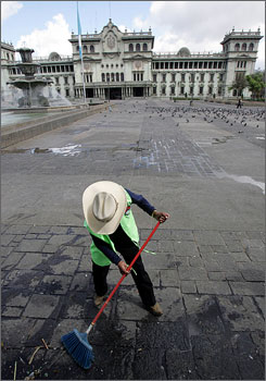 A municipal worker cleans the Peace Square in front of the Presidential Palace before President Bush arrives for a meeting.