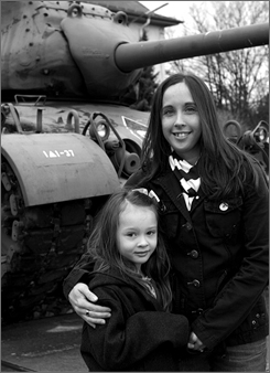 Ginger Gunter and her 6-year-old daughter, Abagail, pose in front of a vintage tank.