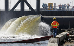 Daren J. Eller watches as pumps put in place by the Army Corps of Engineers pump water from New Orleans' 17th Street Canal to Lake Pontchartra in New Orleans.