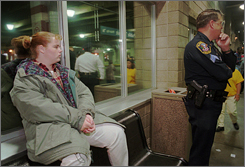 """Then-14-year-old Cassie Agan sat outside the Mall of America in 1996 to protest when it became the first U.S. mall to set a curfew for teens shopping without adults. """"I don't deserve not to come here,"""" Cassie had said. At right, a Bloomington, Minn., police officer kept watch."""
