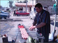 Ali al-Husseini prepares lamb skewers on his sidewalk stand in Baghdad's al-Jadriyah district, which was recently hit by a car bomb.