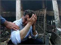 Mohammed Salman grieves at the site of a book market in Baghdad where a car bomb killed his brother and 37 other people March 5.