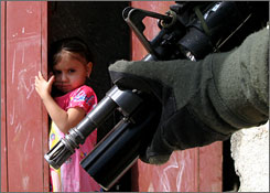 A girl watches a U.S. soldier patrol Sadr City.