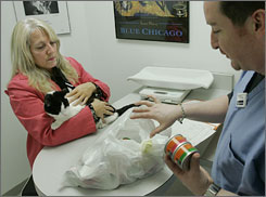 Julie Benesh holds her cat, Truffle, as she talks about the recalled cat food with veterinary technician Daniel Scogin.