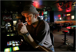 Las Vegas resident and musician Chad Madix lights a cigarette at the Favorites bar in Las Vegas. Bar owner, Ray Medrano chose to close the kitchen rather than ban smoking in his establishment, but he blames Californians for forcing him to make the choice in the first place.