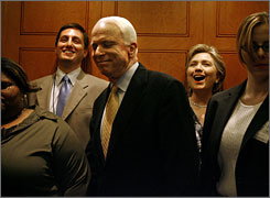 Sen. John McCain, R-Ariz., center, smiles as Sen. Hillary Clinton, D-N.Y., reacts to him getting on the same elevator after a vote at Wednesday in which Democrats successfully voted down 48-50 an ammendment to remove an troop withdrawal date from an Iraq spending bill. The bill passed 51-47 today.