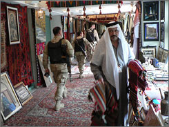 Ali Shadhan displays his rugs at a fair in Baghdad. The Iraq Tourism Ministry used the event to raise funds to resume excavations at historical sites.