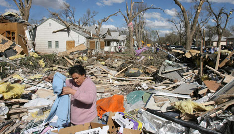 Francisca Magallanes helps salvage clothing items outside her family home in Holly, Colo., Thursday afternoon. A tornado damaged and destroyed countless homes Wednesday evening in the eastern Colorado town of Holly.