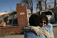 Rene Denis, center, hugs her mother, Nellie Garcia, right, outside Denis' destroyed home in Holly, Colo., Thursday morning. A tornado as wide as two football fields carved a destructive path through this small southeastern Colorado town.