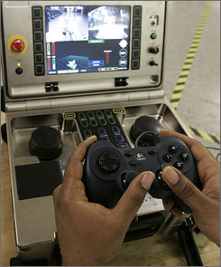 Technician Ken Flucas holds video game type control to operate a robot at GEM City Manufacturing, Monday, in Dayton, Ohio.