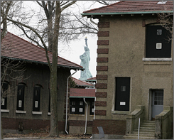 A glimpse of the Statue of Liberty is visible between two stabilized but not yet restored buildings on Ellis Island, N.J.
