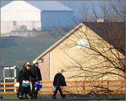 Amish children head to their newly built schoolhouse, background, in Nickel Mines, Pa. The school opened six months from the day, October 2, 2006, that 10 students were shot, five of whom died, in their old schoolhouse that was a short distance away.