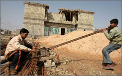 Iraqi youths work at a construction site. A U.S. government audit pulled no punches in a report last month in which it said reconstruction efforts are hampered by widespread violence, corruption and bureaucratic snarls.