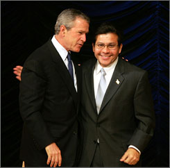 U.S. President George W. Bush embraces U.S. Attorney General Alberto Gonzales as he walks offstage after an address to the Hispanic Chamber of Commerce in 2005.