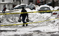 People navigate around a street with downed utility lines in Portland, Maine, on Thursday. A spring storm caused numerous power outages at businesses and residents statewide. Close to 100,000 customers were without power and Central Maine Power Co. predicts it will take until the weekend before all the power is restored.