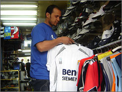 Ali Mohan, owner of the Milano Sport Shop in Baghdad, displays a Real Madrid soccer jersey, one of his best-sellers. The shop has doubled sales of European soccer jerseys since the start of the Champions League last month.