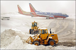 Vehicles plow the runway at Baltimore Washington International Airport while Southwest Airlines jets await deicing during a storm.