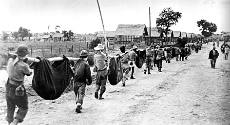 Nearing the end of the Bataan Death March, a thinning line of American and Filipino prisoners of war carry casualties in improvised stretchers as they approach Camp O'Donnell, a Japanese POW camp, in April 1942.