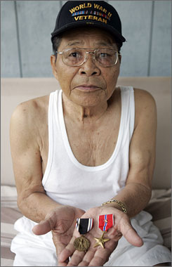 Filipino veteran Manuel Pablo, 88, holds a Bronze Star and POW medal at his home in Waianae, Hawaii, in March. He was awarded the medals while serving the U.S. military in the Philippines during World War II.