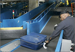 A suitcase is picked out of the line by airport worker Terry Gates after it was diverted by one of the Transportation Security Administration explosive detection devises in the automated inline baggage handling system at Hartsfield Jackson Atlanta International Airport.